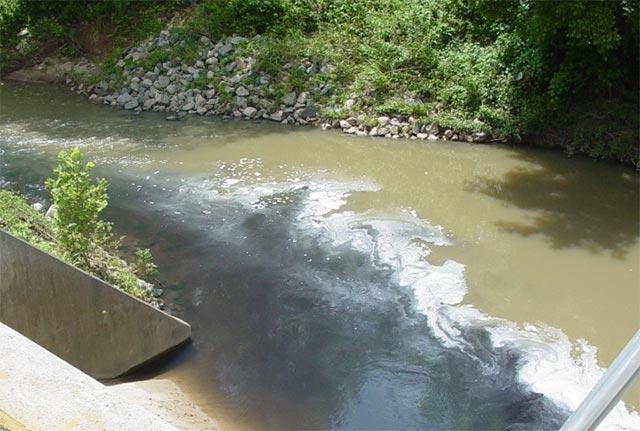 Dark, foamy discharge entering a creek